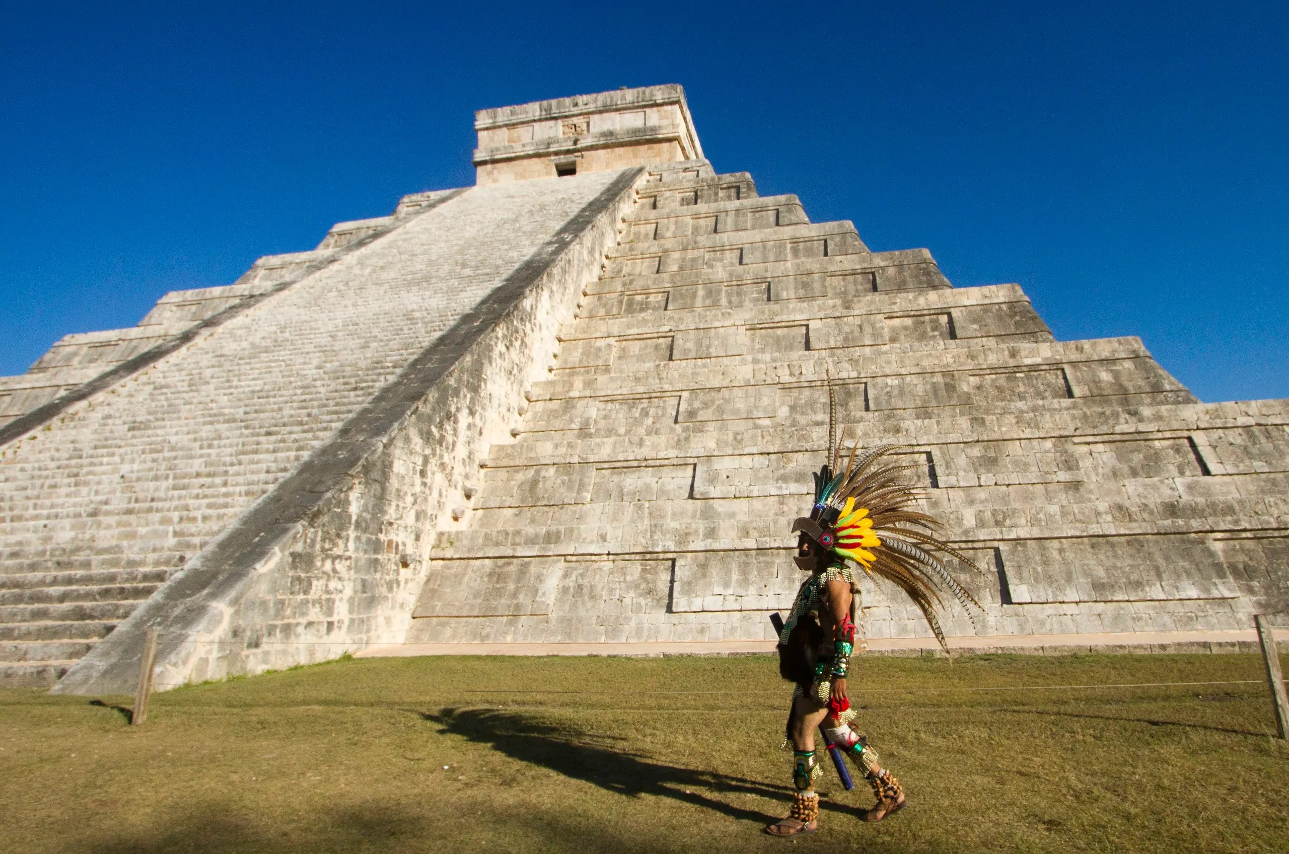 A Mexican man wearing a pre-hispanic costume walk next to the kukulkan pyramid at the Chichen Itza archaeological park, in Yucatan state, Mexico on December 20, 2012. (AFP)