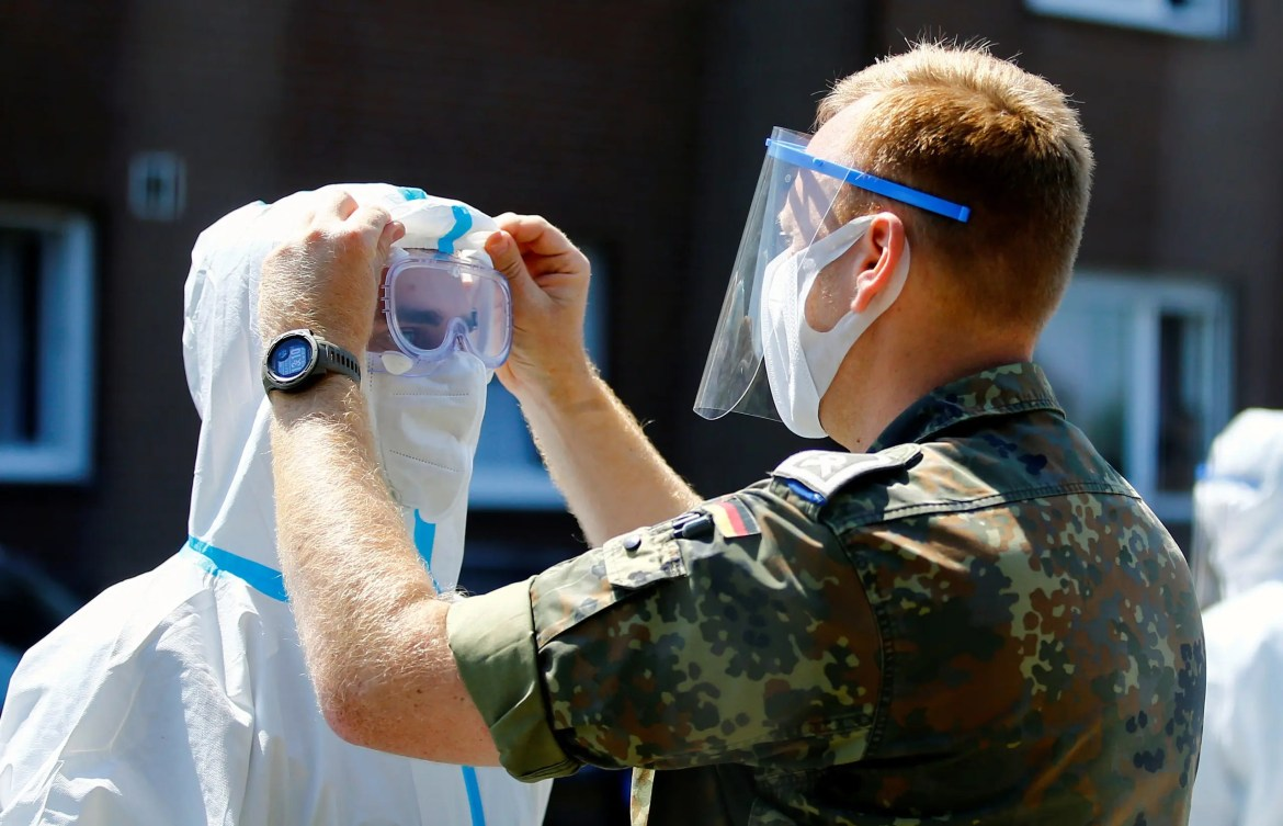 A member of the German Army adjusts the googles of a health professional outside the houses of employees of the Toennies factory, who are under lockdown after a coronavirus disease (COVID-19) outbreak in the meatpacking plant, in Verl, Germany, June 23, 2020. (Reuters)