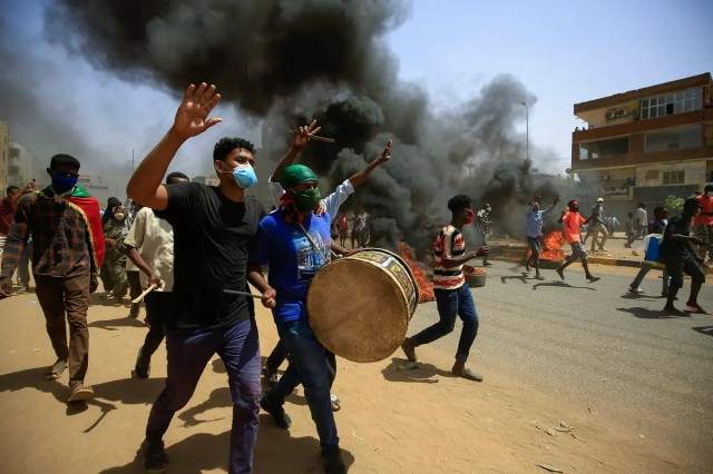 Sudanese demonstrators carrying a drum gesture as smoke billows from burning tires during a protest on Sixty street in the east of the capital Khartoum, on June 30, 2020. (AFP)