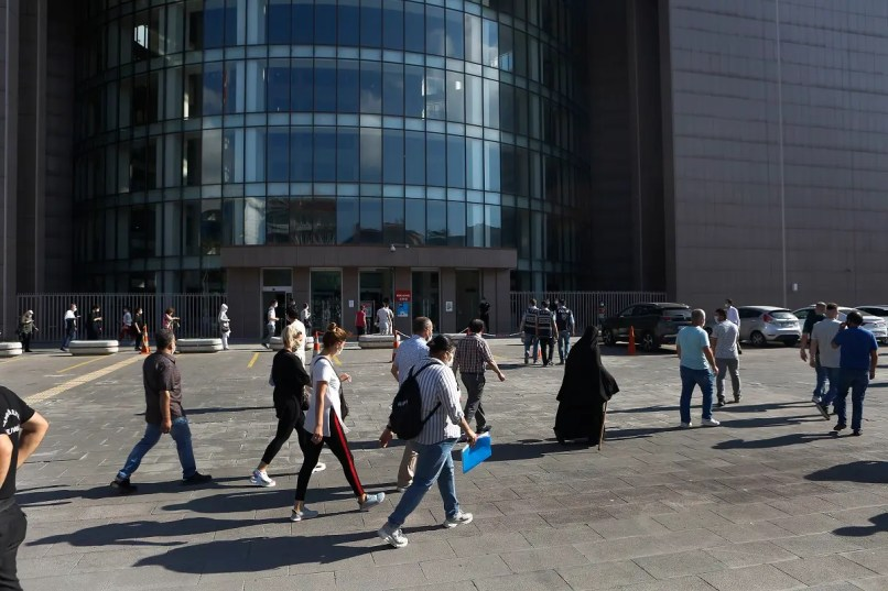 People walk outside a court in Istanbul, Friday, July 3, 2020, where the trial began for defendants accused of smuggling former Nissan Motor Co. chairman Carlos Ghosn out of Japan. (AP)