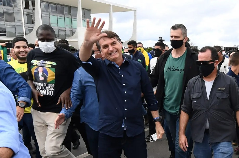 In this file photo taken on May 24, 2020 Bolsonaro greets supporters upon arrival at Planalto Palace in Brasilia, amid the COVID-19 coronavirus pandemic. (AFP)