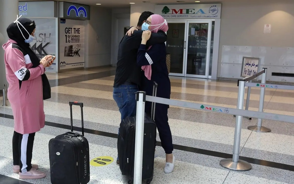 A woman wearing a face mask embraces a man before she heads to board a plane at Beirut International airport, Lebanon July 17, 2020. (Reuters)