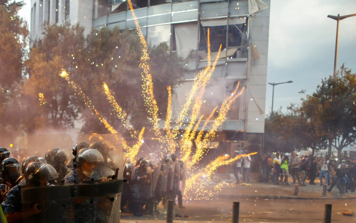 Fireworks are set off in front of police officers during anti-government protests that have been ignited by a massive explosion in Beirut, Lebanon August 10, 2020. REUTERS/Thaier Al-Sudani