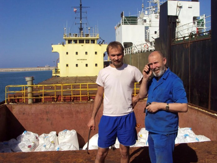 Boris Prokoshev, captain of the cargo ship Roussos and with him Boris Mussenchak stand next to a cargo area in Beirut.