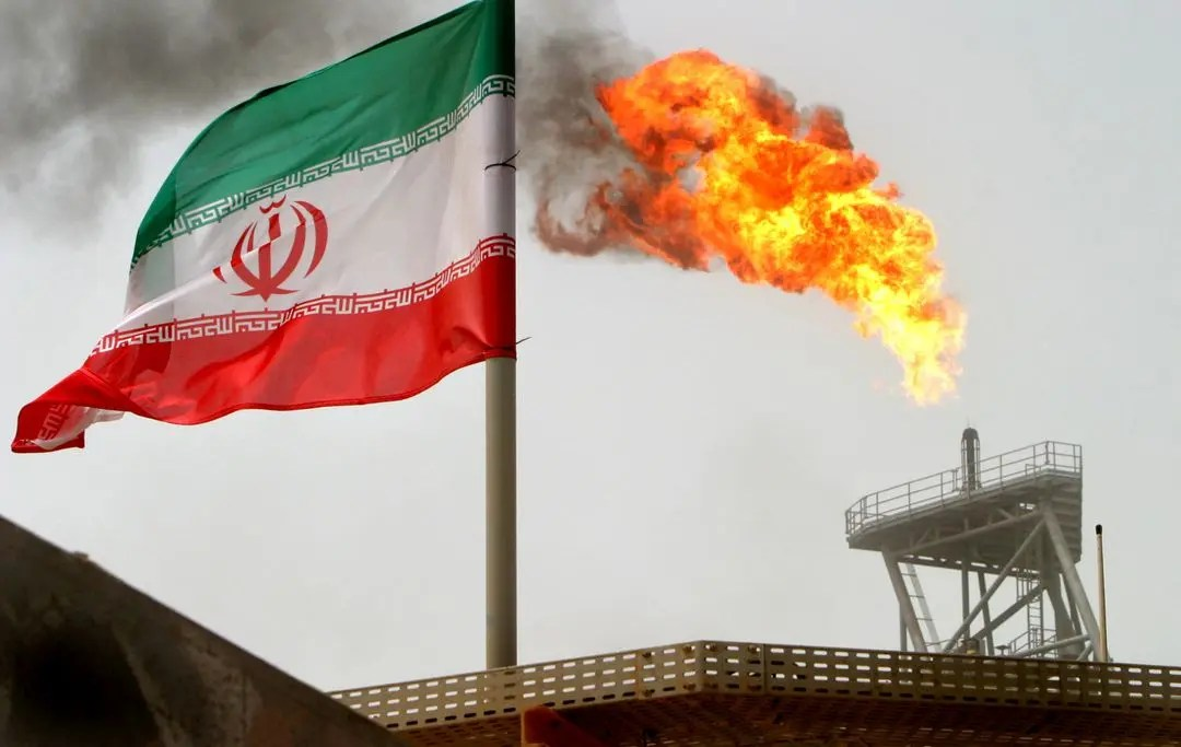A gas flare on an oil production platform is seen alongside an Iranian flag in the Gulf July 25, 2005. (Reuters)