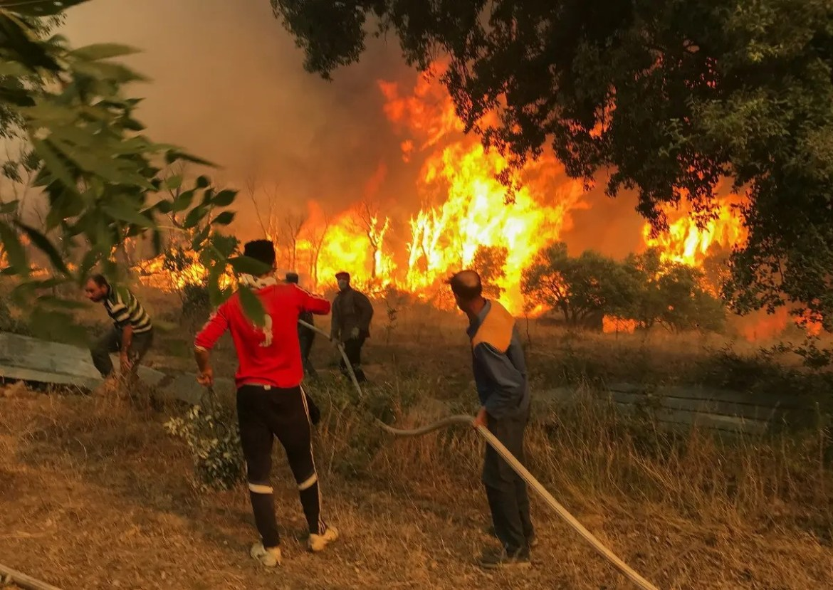 Villagers carry a hose as they try to put out a wildfire, in Achallam village, in the mountainous Kabylie region of Tizi Ouzou, east of Algiers, Algeria. (Reuters)