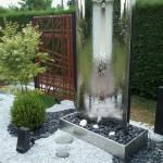Fontaine d'extérieur avec panneaux bois, massif minéral et intégration végétale