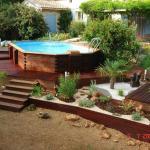 Piscine bois avec terrasse périphérique en palier, ponton d'accès au solarium et massifs et jardinières surfacés gravier et écorce