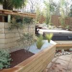 Intégration de spa avec terrasse bois, bardage et massif minéral