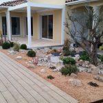 Massif minéral avec olivier en pièce principale en abords de terrasse bois piscine.