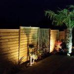 Panneaux en bois positionné en cloture avec bande de plantation et éclairage paysager en abords de terrasse.