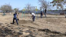 Spreading dirt to fill in ruts on the playground