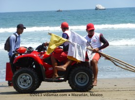 Lifeguards taking down the warning flags.