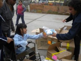 Voluntario entregando zapatillas a niña