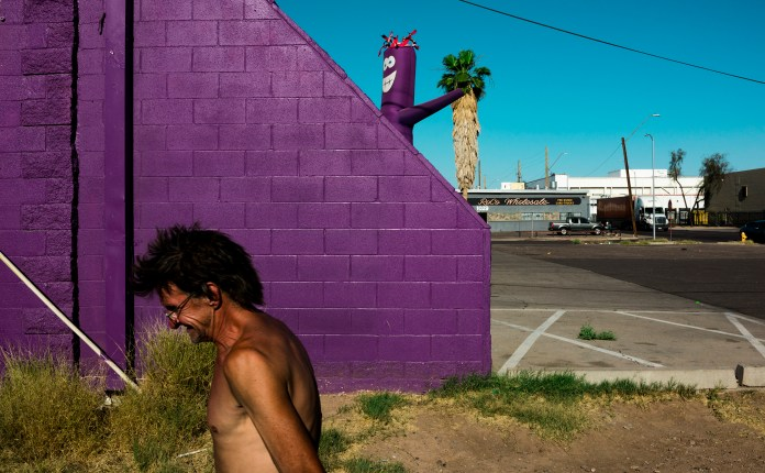 a man in front on a purple inflatable doll in Robert LeBlanc A New America