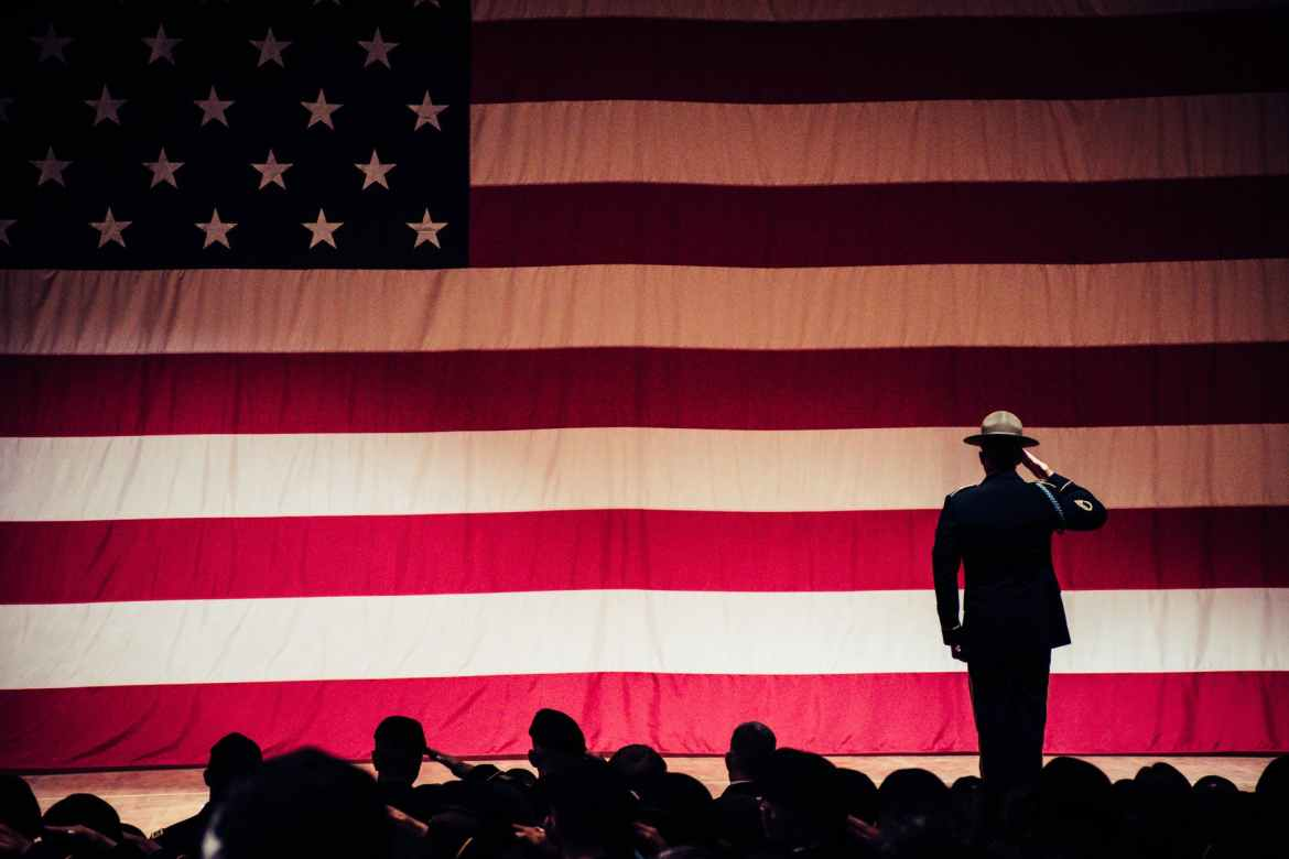 man standing on stage facing an american flag