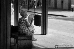 Mujer con abanico en la parada del bus