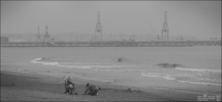 Madre jugando en playa gris