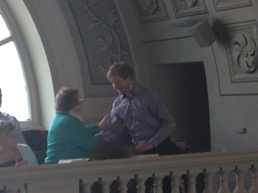 Thomasz Piętak receiving the Rothgeb Memorial Grant from Anne Peschek at the 7 June 2015 Sunday Service.