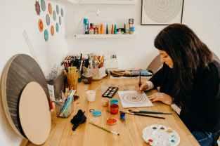 woman painting mandala design on a white paper