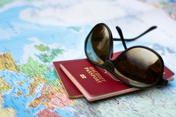 Two passports and sunglasses lay on a map of Europe
