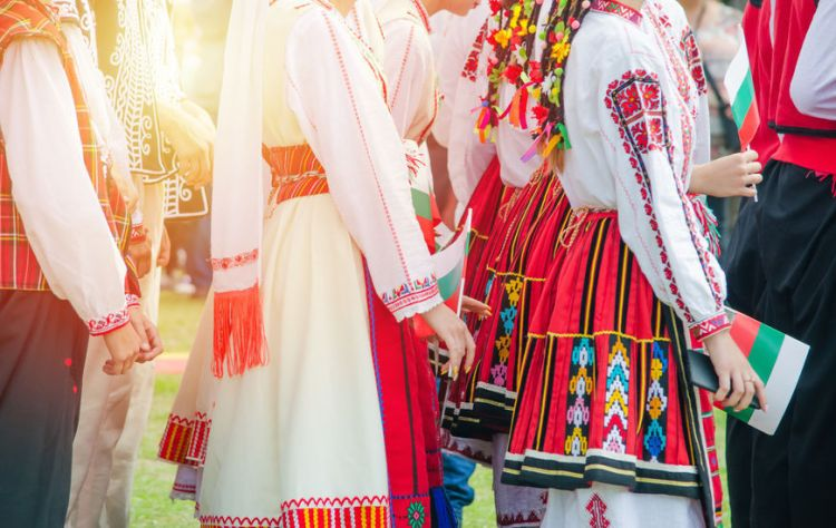 Unrecognizable irls in ethnic Bulgarian costumes with colorful ornament