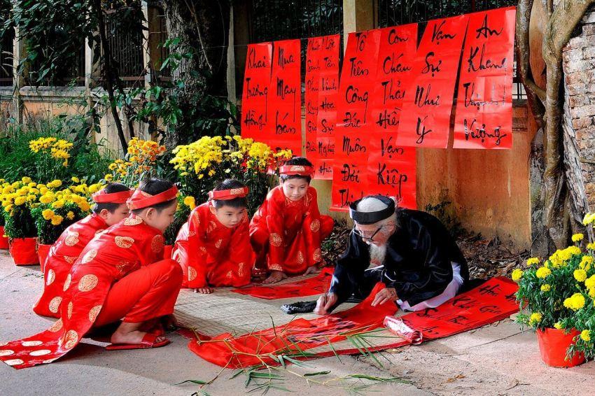 Нарядно одетые вьетнамские дети помогают дедушке