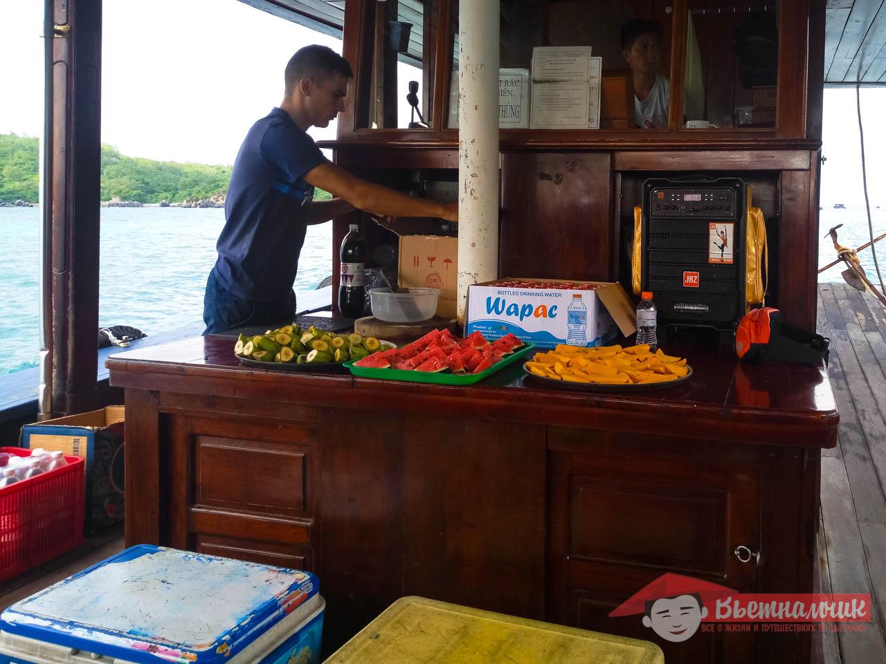 Гид нарезает фрукты для туристов