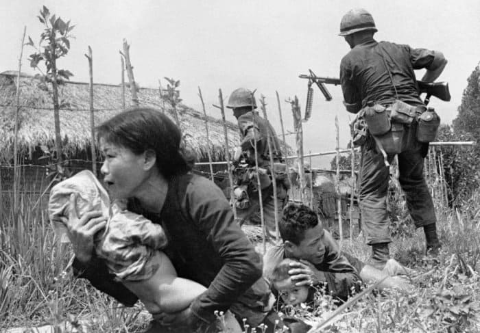 Under sniper fire, a Vietnamese woman carries a child to safety as US marines storm the village of My Son, near Da Nang, searching for Vietcong insurgents, 25 April 1965. As was typical in such situations, the men of the village had mostly disappeared, and the remaining villagers revealed little when questioned Photograph: Eddie Adams/AP