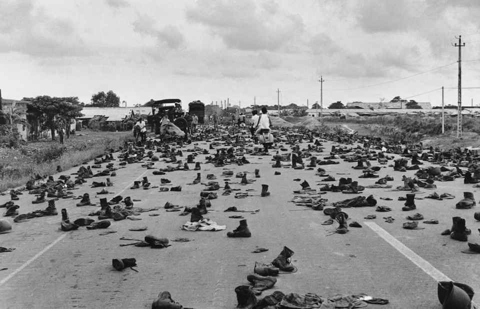 "April 30, 1975 Combat boots litter the road on the outskirts of Saigon, abandoned by ARVN soldiers who shed their uniforms to hide their status. ""I'll never forget the shoes and the loud 'thump, thump, thump' sound as we drove over them,"" recalled the photographer. ""Decades of war were over and we finally had peace."" IMAGE: DUONG THANH PHONG/ANOTHER VIETNAM/NATIONAL GEOGRAPHIC BOOKS"