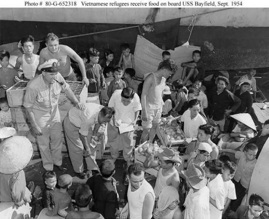 Các thủy thủ Pháp chia phần ăn cho đồng bào miền Bắc di cư (vào Nam) trên tàu USS Bayfield (APA-33) năm 1954.