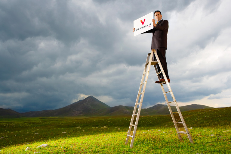 Make money on YouTube — man standing on ladder with sign
