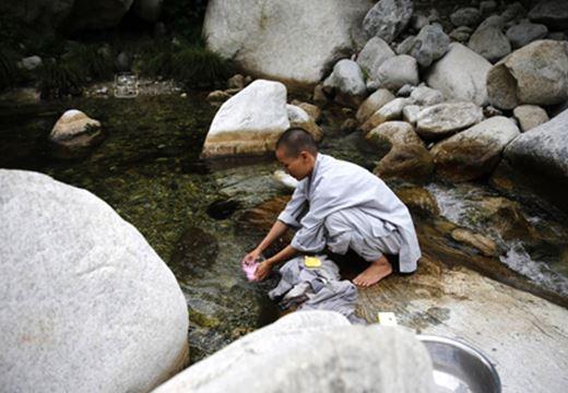 ABuddhist nun washing clothes in a stream