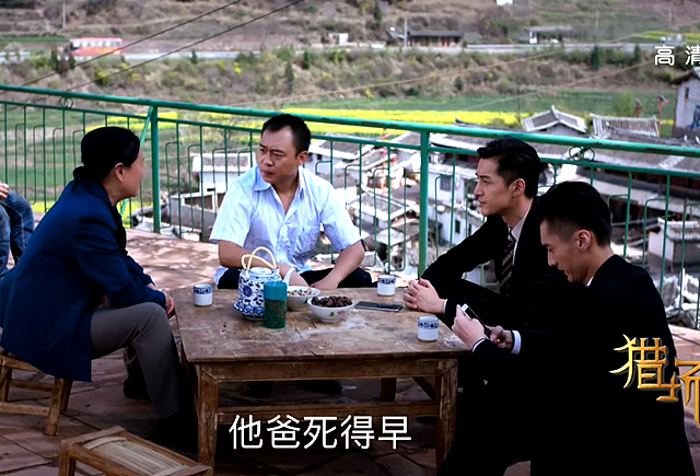 Zheng Qiudong talking to village head and village teacher over tea