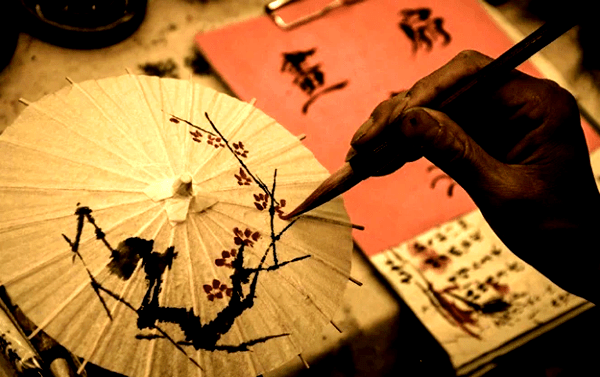 painting winter plum flowers on a paper umbrella