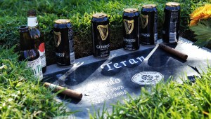 Firefighters grace Teran's head stone with cigars and beers at his burial site in Riverside.