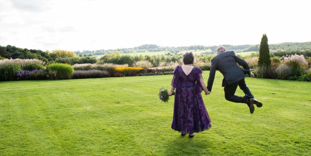me in purple wedding dress with husband jumping with backs to camera Abbeywood garden Cheshire