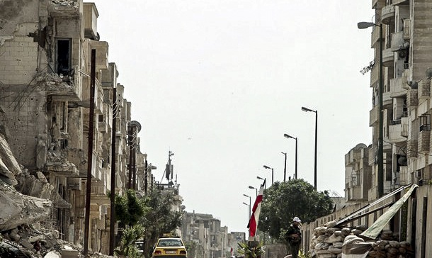 A taxi drives past Syrian soldiers manning a checkpoint at the entrance of al-Karama area in the Bab Amro neighborhood of Homs on May 2, 2012. (File photo by FreedomHouse)