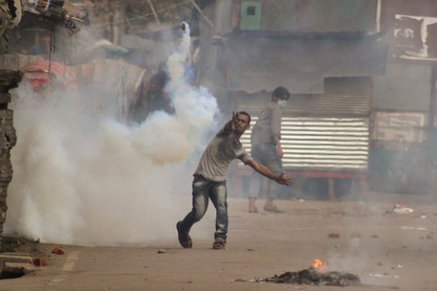 A protester in Bangladesh throws stones at police during a protest. (Photo via bdnews24.com)