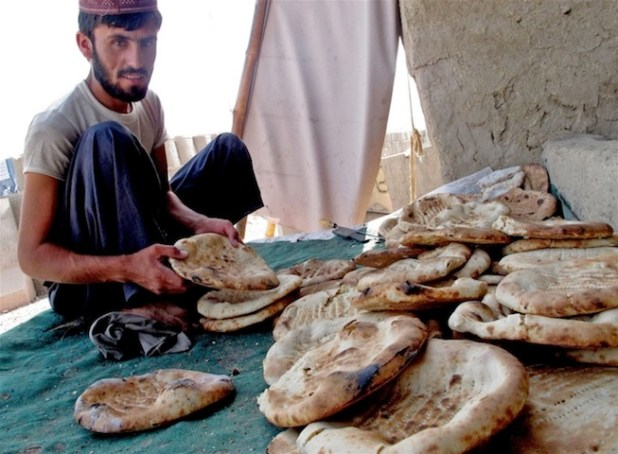 A baker sorts out freshly baked traditional Afghan naan bread in Arghandab Valley, southern Afghanistan. (Photo by Jason Gutierrez via IRIN)