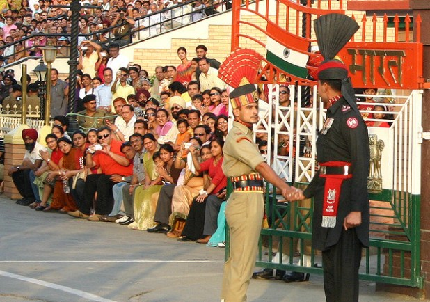 (From L to R) Indian and Pakistani soldiers shake hands at the two countries' border at Wagah, near Pakistani city of Lahore. (Photo by joshuahsong, Creative Commons License)