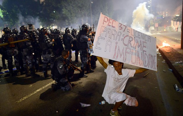 A demonstrator displays a banner against PEC37 a draft bill limiting the prosecutor's capacity of investigation in cases of corruption as anti riot police officers fire rubber bullets after clashes erupted during a protest against corruption and price hikes, on June 20, 2013, in Rio de Janeiro. (Photo by David Foster, Creative Commons License)