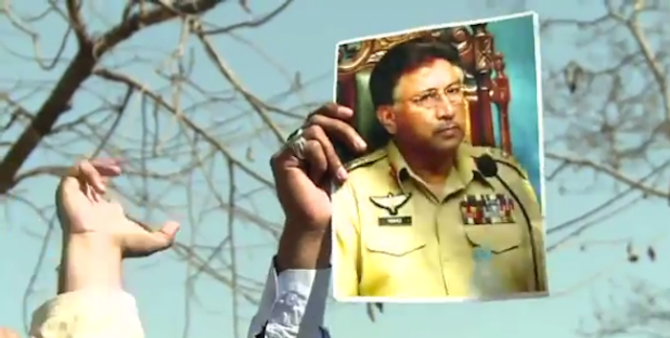 A supporter of General Pervez Musharraf holds his photo outside the court in Islamabad on March 14. (Photo from video stream)