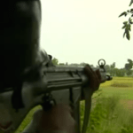 """A Pakistani soldier aims at Indian territory from his check post on the country's """"Working Boundary"""" with India. (Photo from videostream)"""