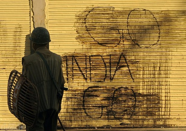 An Indian policeman looks at an anti-India slogan on shop shutter in Srinagar, the summer capital of Indian-administered Kashmir. (Photo by Kashmir Global, Creative Commons License)