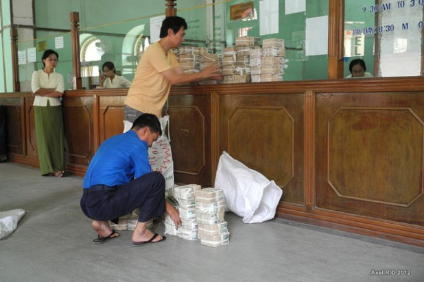 Businessmen make a bank deposit at a bank in Yangon. (Photo by Axel Drainville, Creative Commons License)