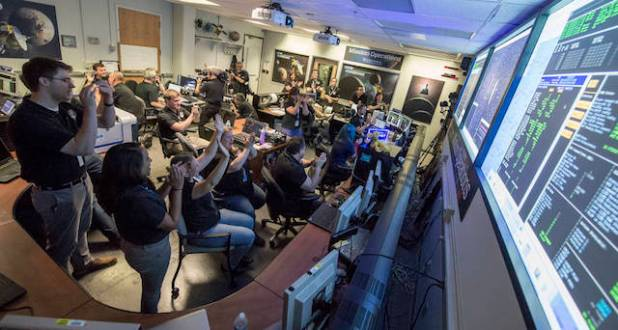 New Horizons Flight Controllers celebrate after they received confirmation from the spacecraft that it had successfully completed the flyby of Pluto, Tuesday, July 14, 2015 in the Mission Operations Center (MOC) of the Johns Hopkins University Applied Physics Laboratory (APL), Laurel, Maryland. (Photo Credits: NASA/Bill Ingalls)