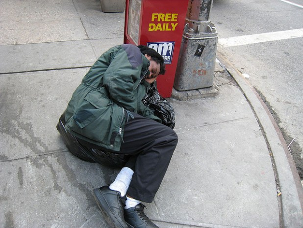 A homeless man sleeping on a New York street. (Photo by Teknorat, Creative Commons License)