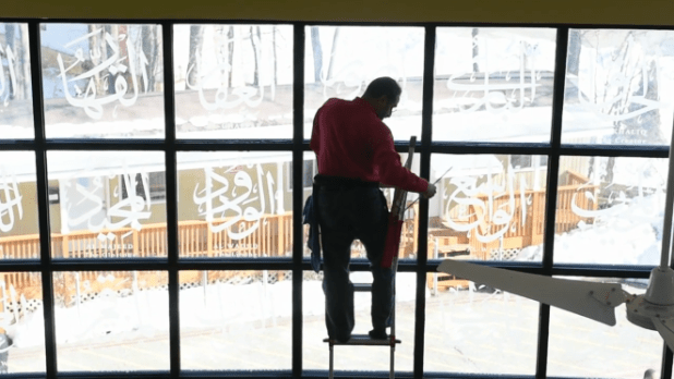 A worker cleans windows of the Islamic Center of Baltimore ahead of President Barack Obama's visit. (Photo via video stream)