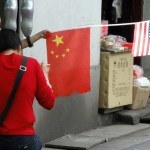 A boy hold Chinese and American flags in Shanghai, China. (Photo by Eric Pesik, Creative Commons License)